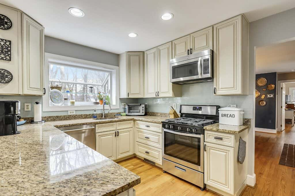 a safe, functional, and updated cream kitchen cabinets with green subway glass tiles, granite countertops and grey walls.