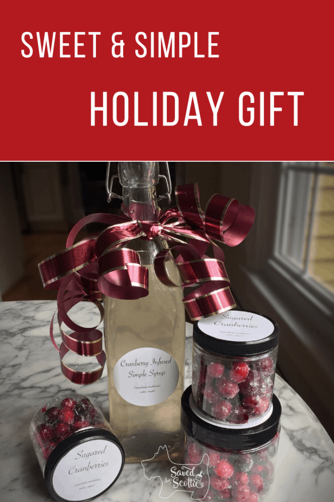 Pinnable image for sweet and simple holiday gift showing a bottle of cranberry infused simple syrup with jars of sugared cranberries around it on a marble table top.