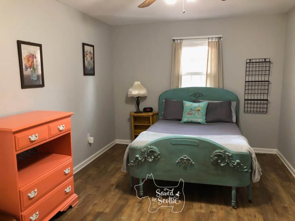 The Goat Loft bedroom with grey walls, ornate wooden bed painted teal, coral dresser, mustard yellow nightstand with  lamp and clock on it. Tiered basket rack next to bed on right, window with curtains behind bed and two floral prints on the left wall that tie all the colors together.