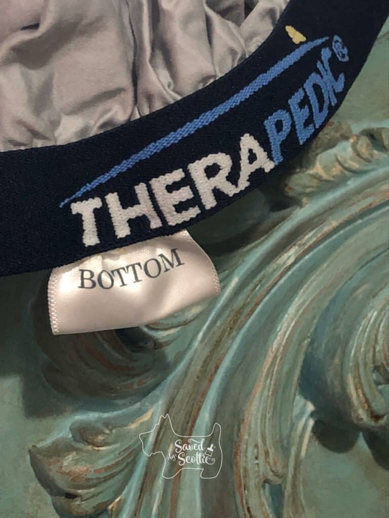 """grey therapedic sheet with thick branded elastic around the edge. tag on sheet reads """"bottom"""" and mouldings of teal footboard are in background."""