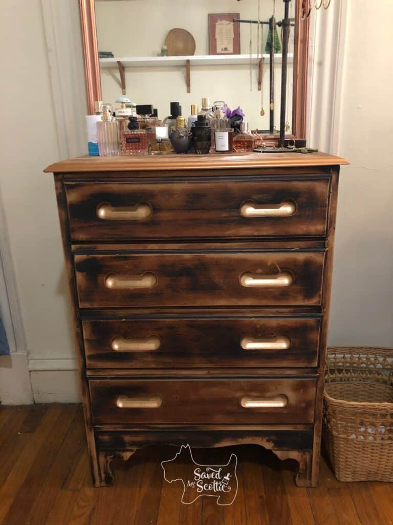 the copper painted dresser in place at a home with perfume bottles and self care products arranged well. A mirror is above it that reflects the other wall of the room that has a high shelf with various items of decor on it.