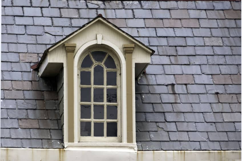 An old, ornate window surrounded by gray slate roof shingles in need of home maintenance.