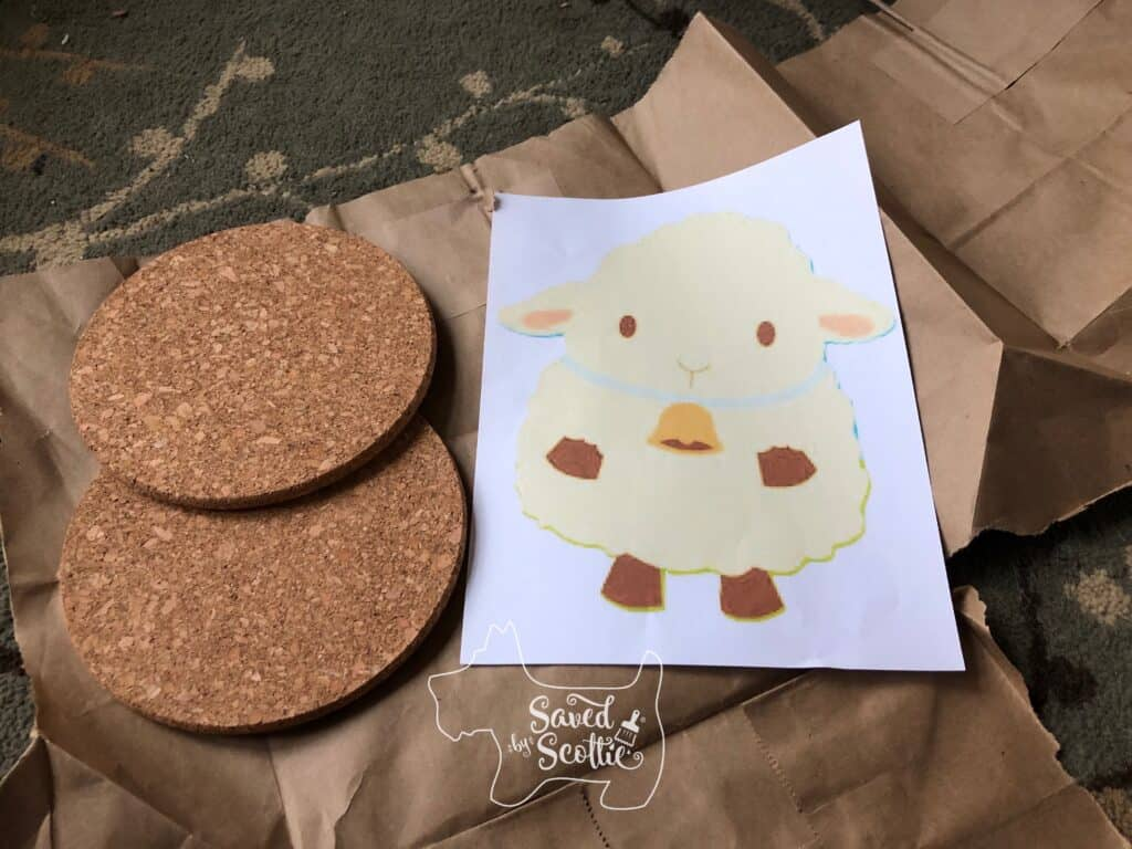 2 round cork trivets next to a print out of a sheep image laying on a piece of kraft paper ready for creating the perfect BFF gift