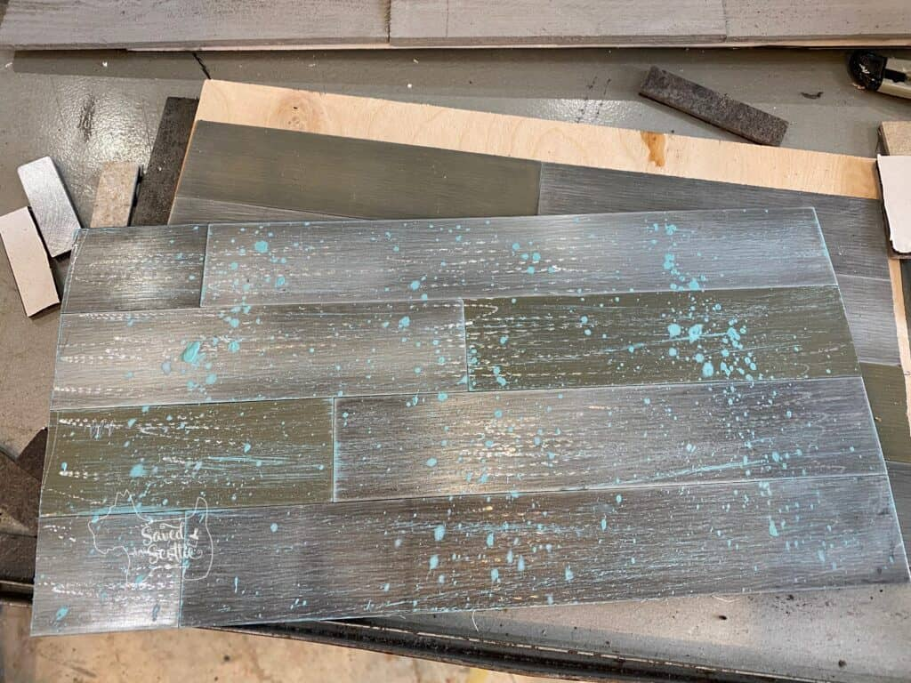 reclaimed metal tile splatter painted with teal acrylic paint.