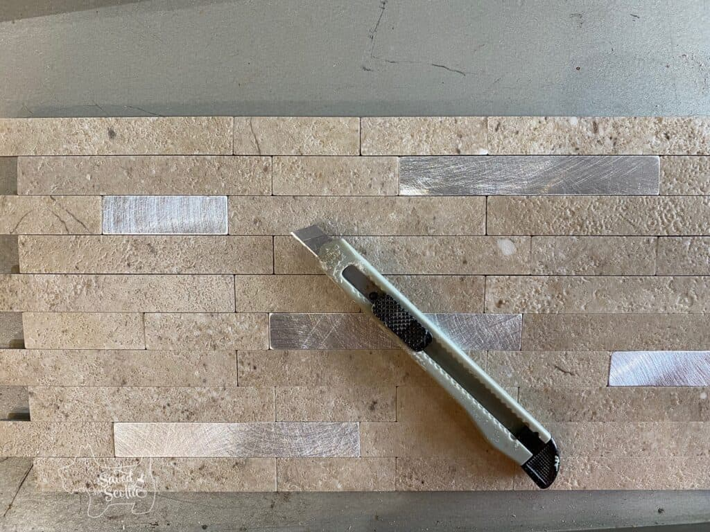 small snap blade utility knife laying on an Aspect Tile stone and metal collage tile.