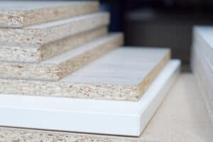 PARTICLE BOARD. Wood panels of different thicknesses and colors. Furniture fittings for furniture production stacked