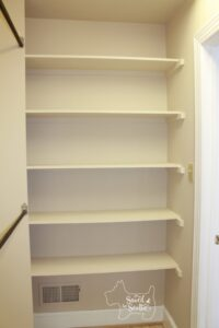 shelves in closet with clothing bar to the left