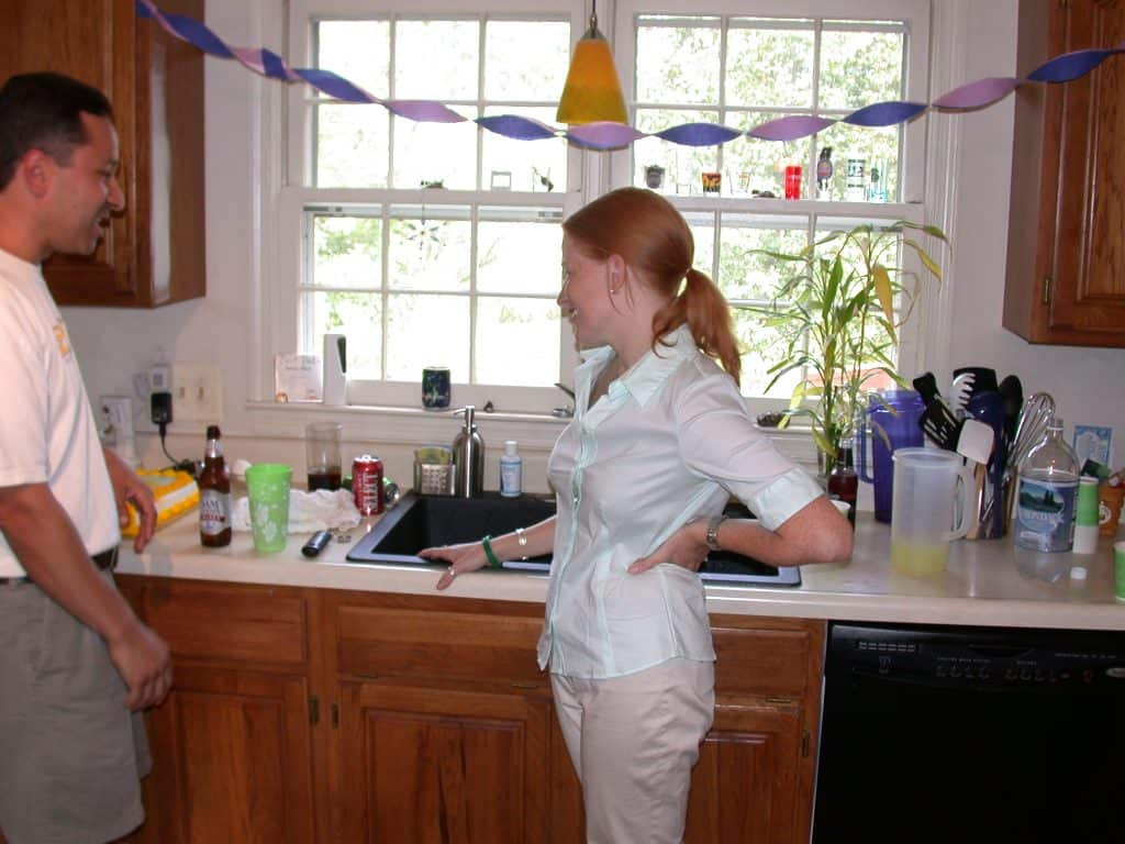woman in kitchen at a party. Standing at sink and talking to a man.