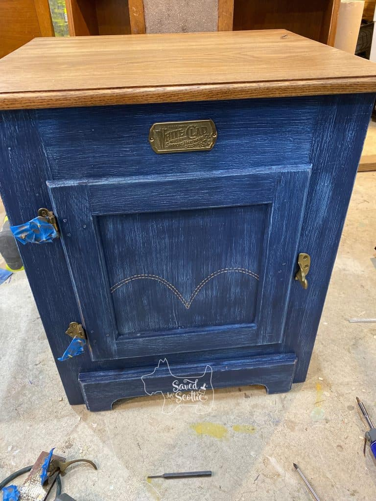 white clad furniture side table in process Inspired by denim jeans. two tone with iconic levis pocket pattern painted on door. brass hardware