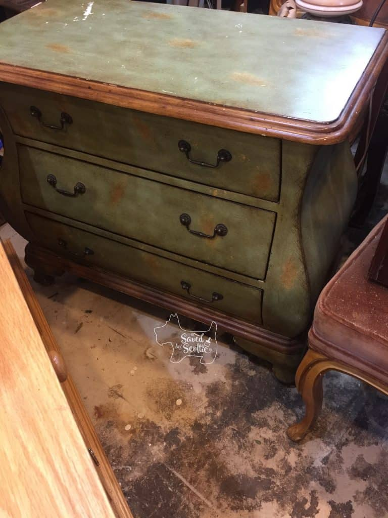 bombay chest redo before shot- dark and dingy green and tan mottled bombay chest with dark metal handles and brown trim. top is chipped and worn.