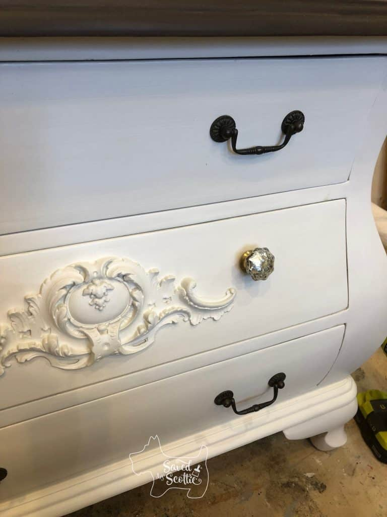close up of drawer front on painted bombay chest with mercury glass knobs in place. Original darker swing pulls are visible on bottom drawer.
