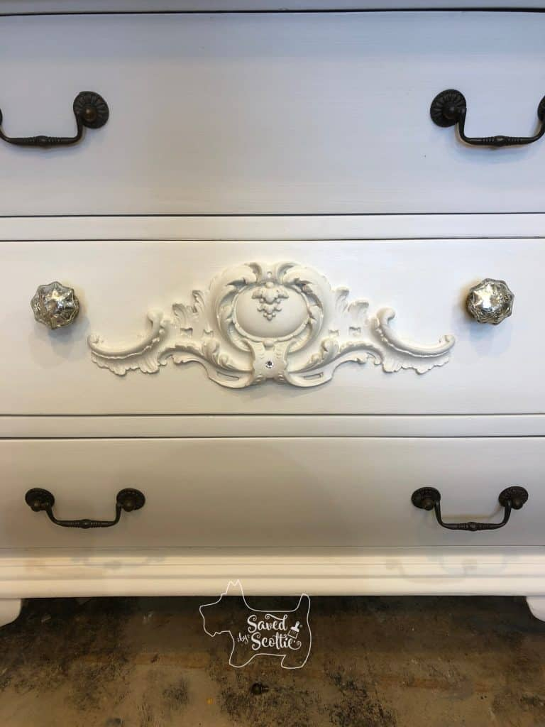 close up of moulding piece on drawer front with Swarovski crystal attached to bottom indentation original handles and some of the new mercury glass knobs are visible as well. In workshop environment and concrete floor visible