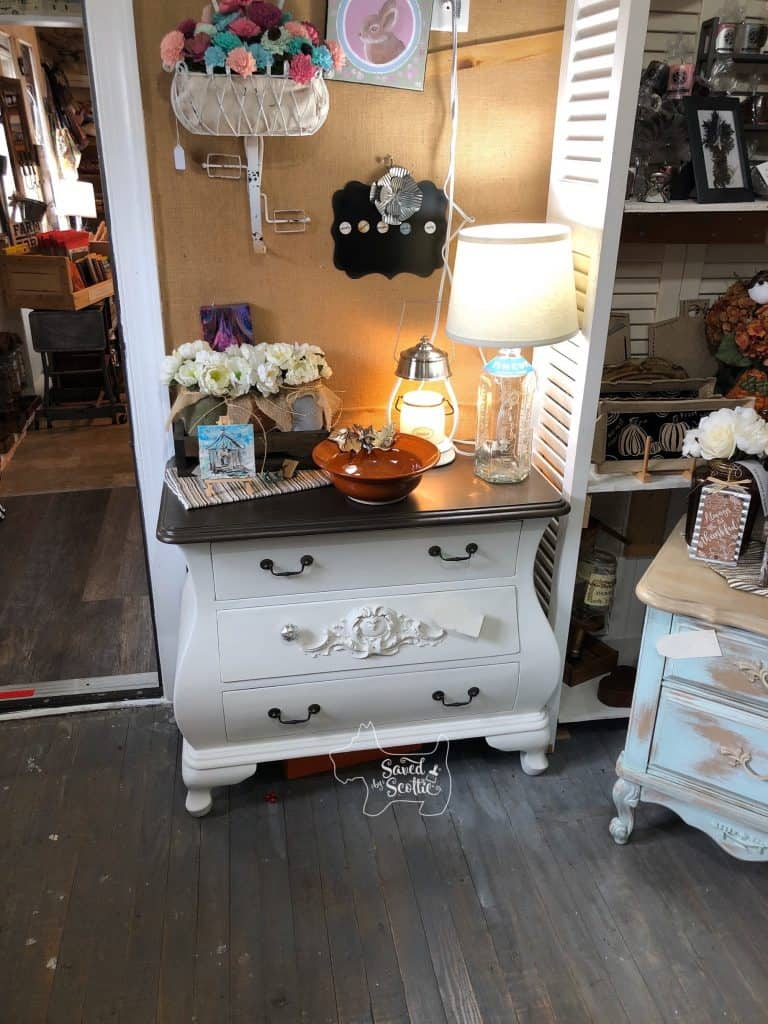 finished white bombay chest redo in store setting with a lamp, pottery bowl, flowers, and other small items displayed on and around it.