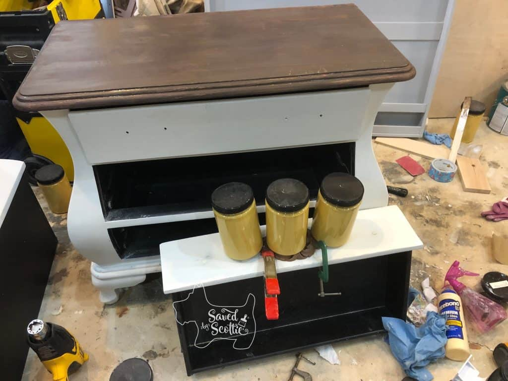 bombay chest in workshop environment with painted brown top. drawer on floor with 3 quarts of paint placed on top of it and two clamps holding the moulding piece down to cure overnight.