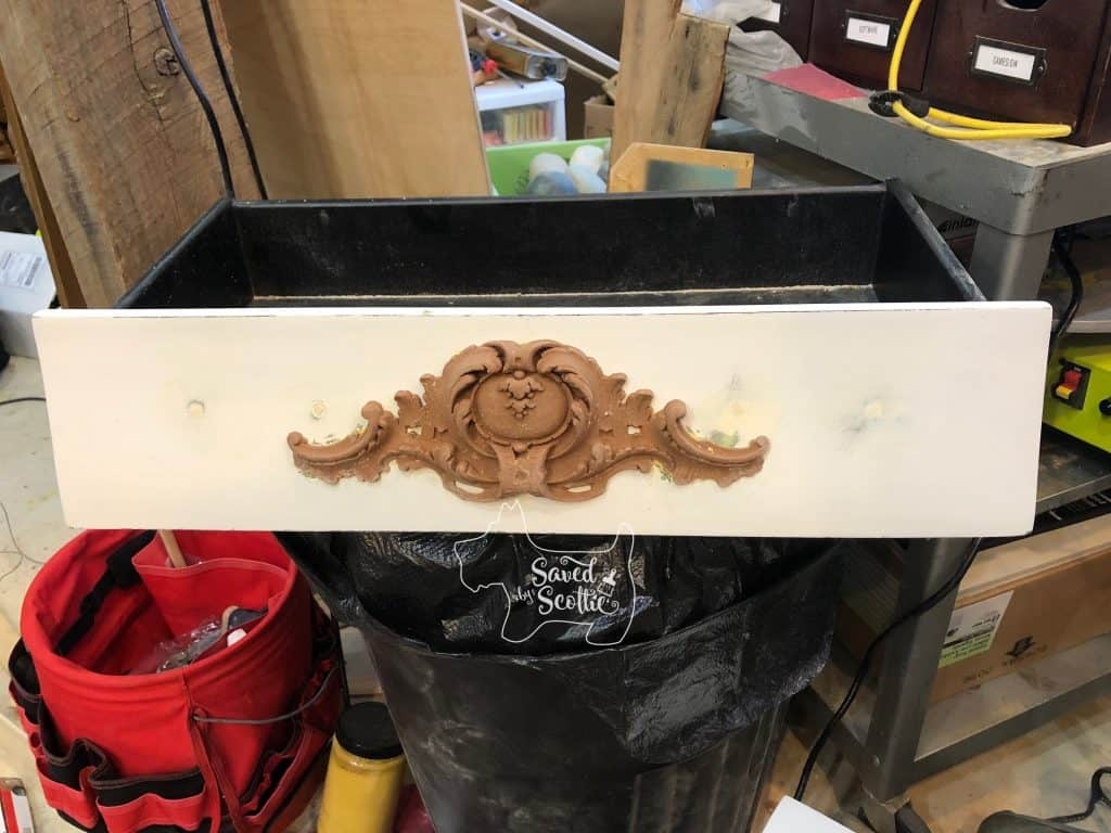 Moulding attached to bombay chest drawer with holes filled on the side and ready to be painted.
