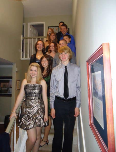 a group of teens gathered on interior steps before a dance.