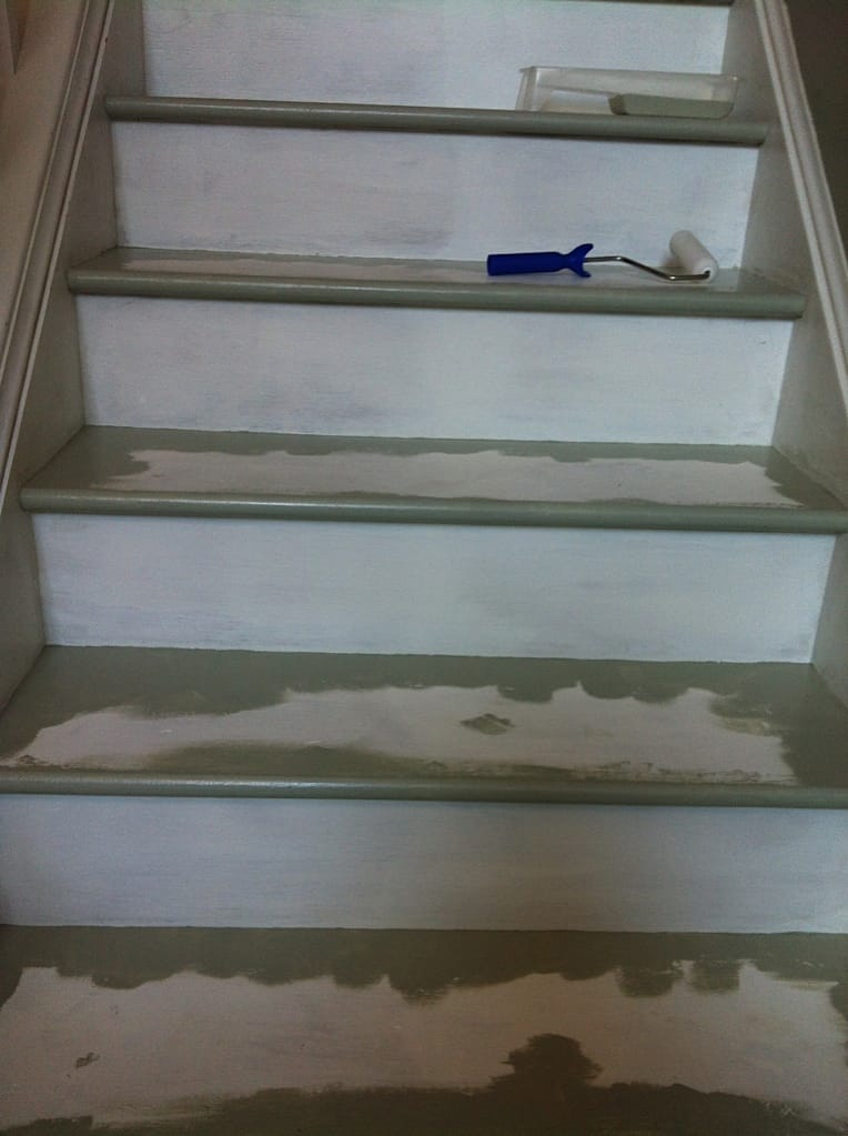painted steps in process with roller and paint tray supplies laying on steps.