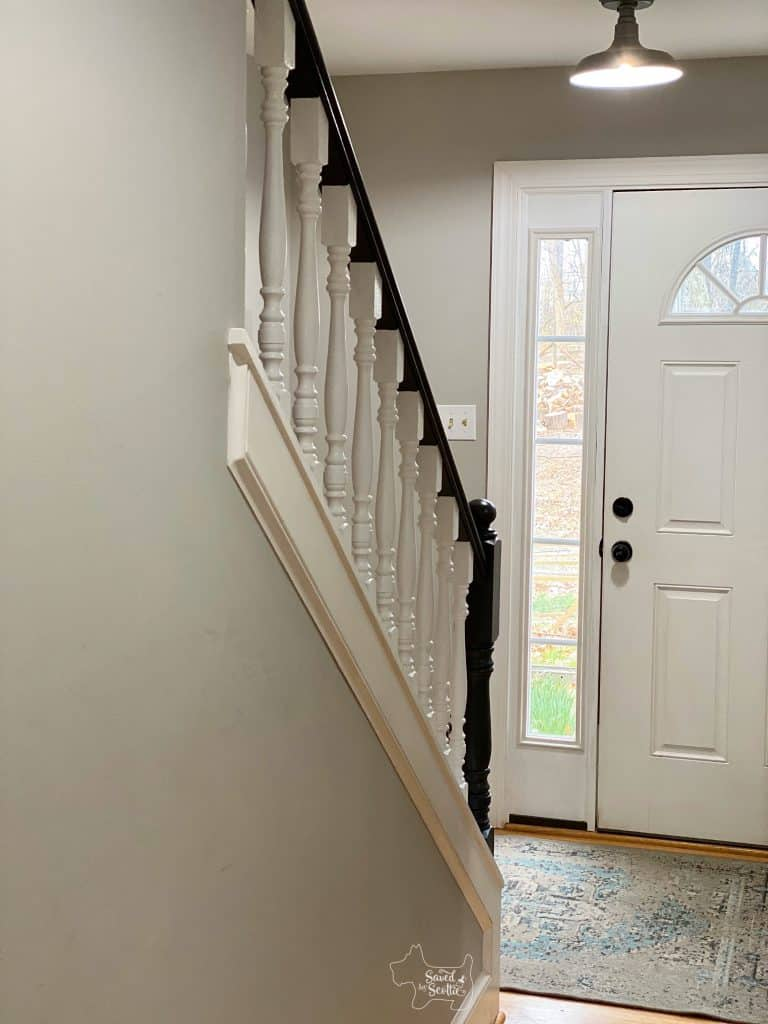 "Finished view of ""new"" painted stair railings down hall to front door of home."