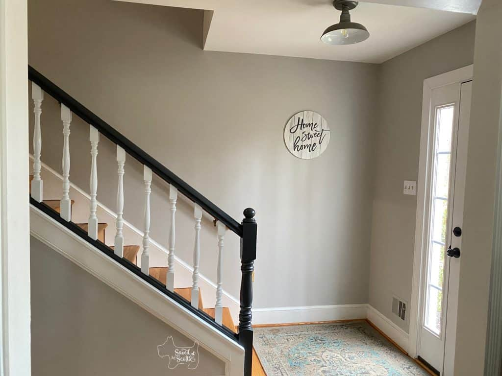finished painted stair railings in home. Grey walls with Home Sweet Home in wooden circle hanging on wall.