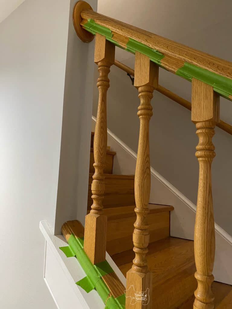 golden oak balusters taped off with green frog tape waiting to be painted