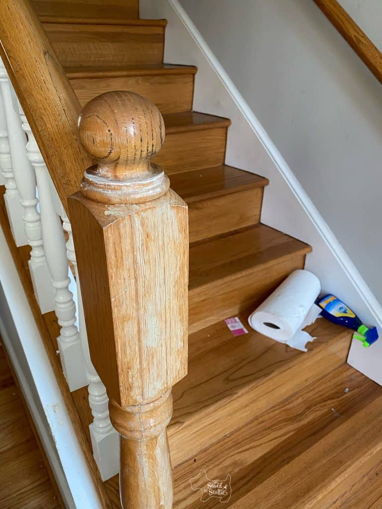 wood filler in long cracks on newel post. Painted balusters and paper towels and cleaner on the steps in the background
