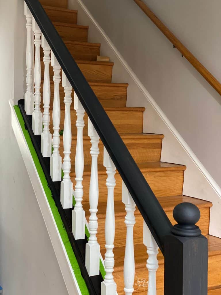 painted stair railings in process with white balusters and black matte hand an shoe rails. Painted with chalk-finish paint as a primer