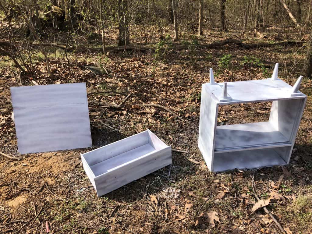 cabinet in pieces on ground after spray paint primer.
