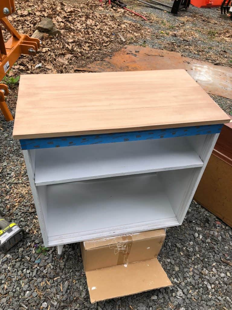 full view of painted cabinet with stain coat on top.