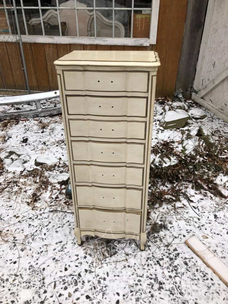 lingerie chest before. white french provincial style no handles on it. in snow in front of barn workshop