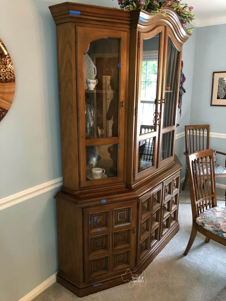 Wood china cabinet in a dining room of client's home. full of china and light blue walls.