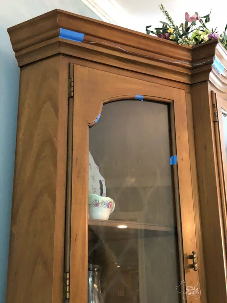 close up of top of china cabinet with tape and chalk lines on places to consider painting