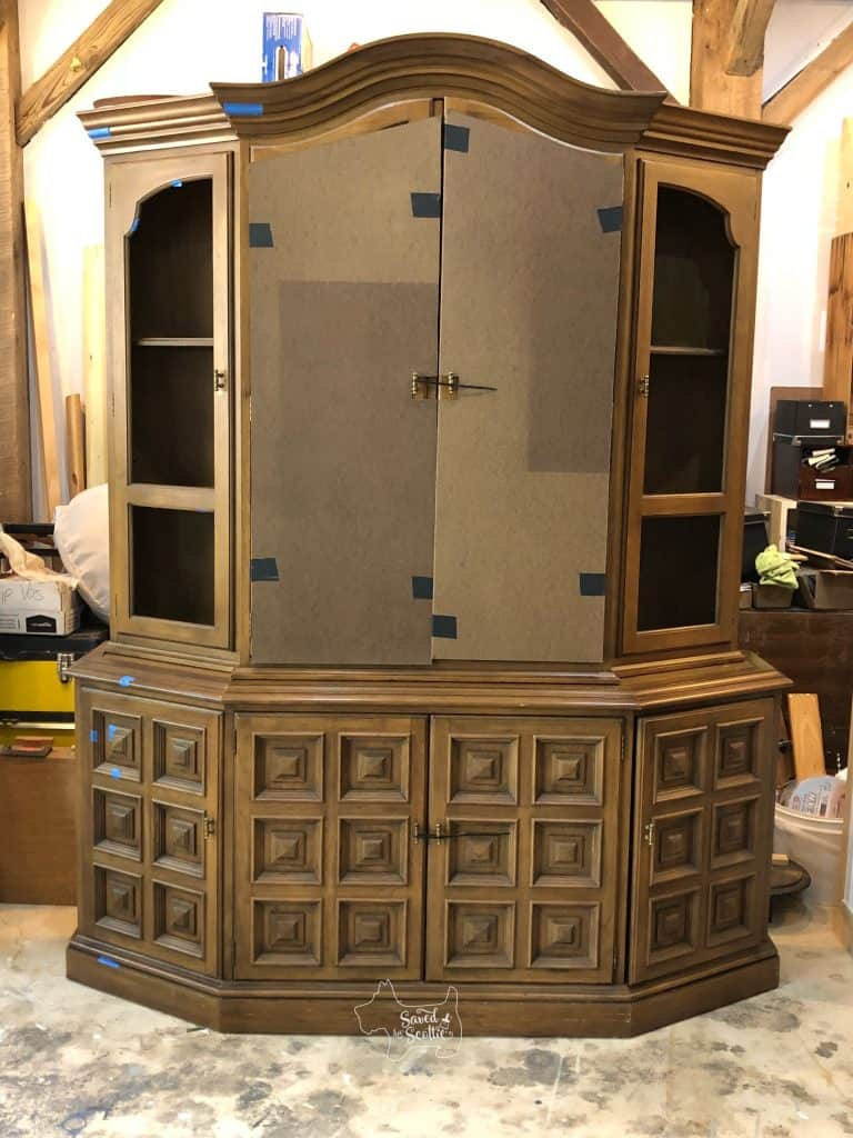 full view of china cabinet in workshop setting with wood panels over the doors after being dropped off by moving company.