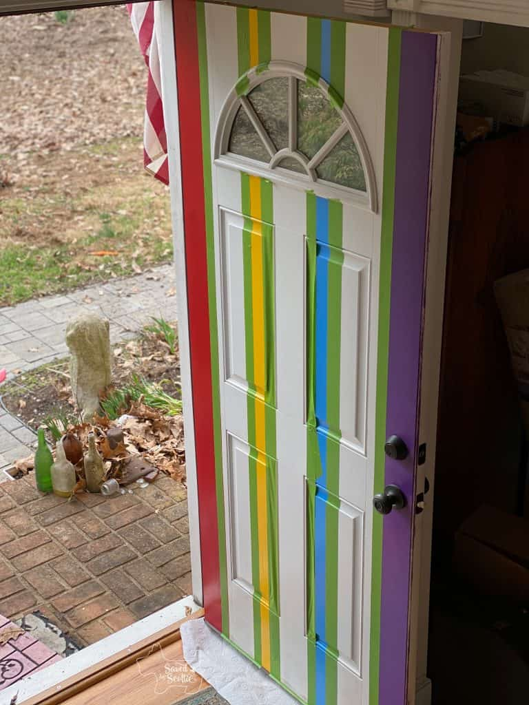 partially painted front door taped out for final lines with frog tape.