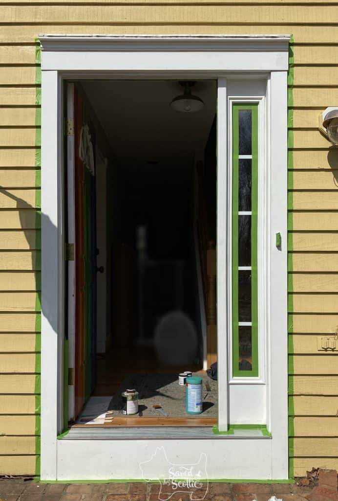 front door trim taped out with frog tape and ready to be refreshed with white paint.