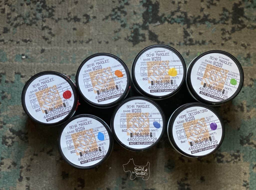 collection of sample size Behr paints from Home Depot in the colors of a rainbow- No more drama red, Japanese Koi orange, Soft boiled yellow, springview green, peaceful river blue, charter blue indigo, and virtual violet.