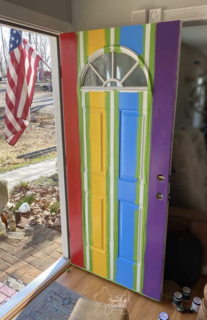 Open front door with green Frog Tape lines and painted stripes of red, yellow, blue, and violet. white spaces in between and US flag hanging outside.