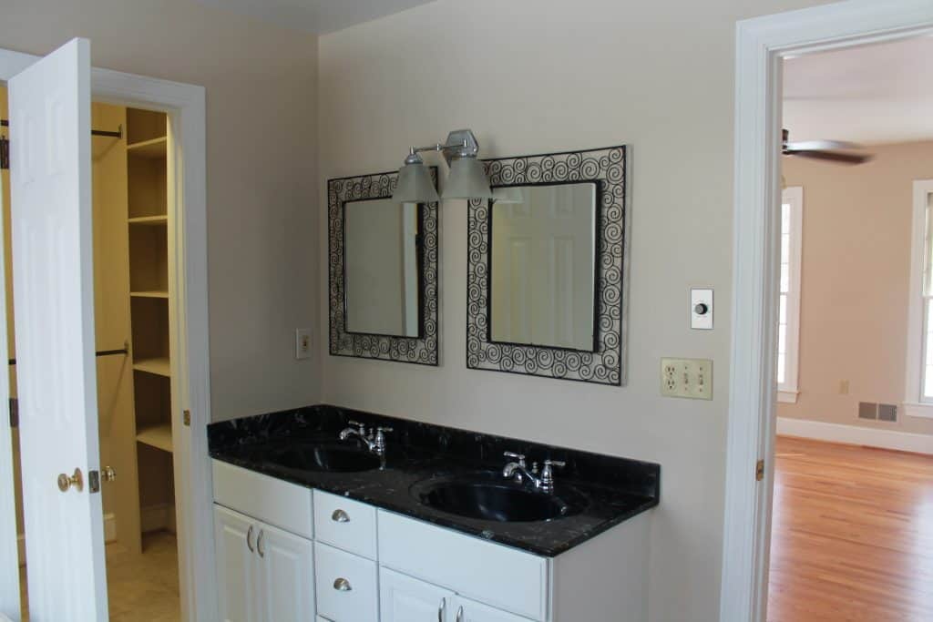 master bathroom with entrance to closet on left double sink with iron mirrors. white vanity and black marble countertops