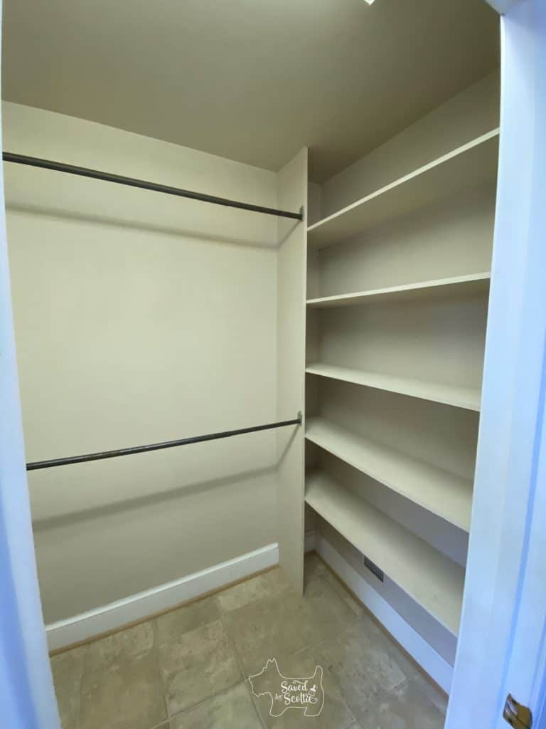 wide angle shot of wall of shelves on right and double hanging in master closet