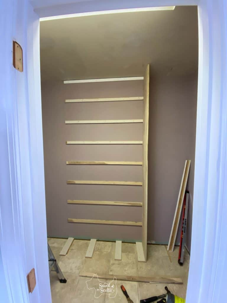 wall of closet makeover with rear shelf supports and one side up.
