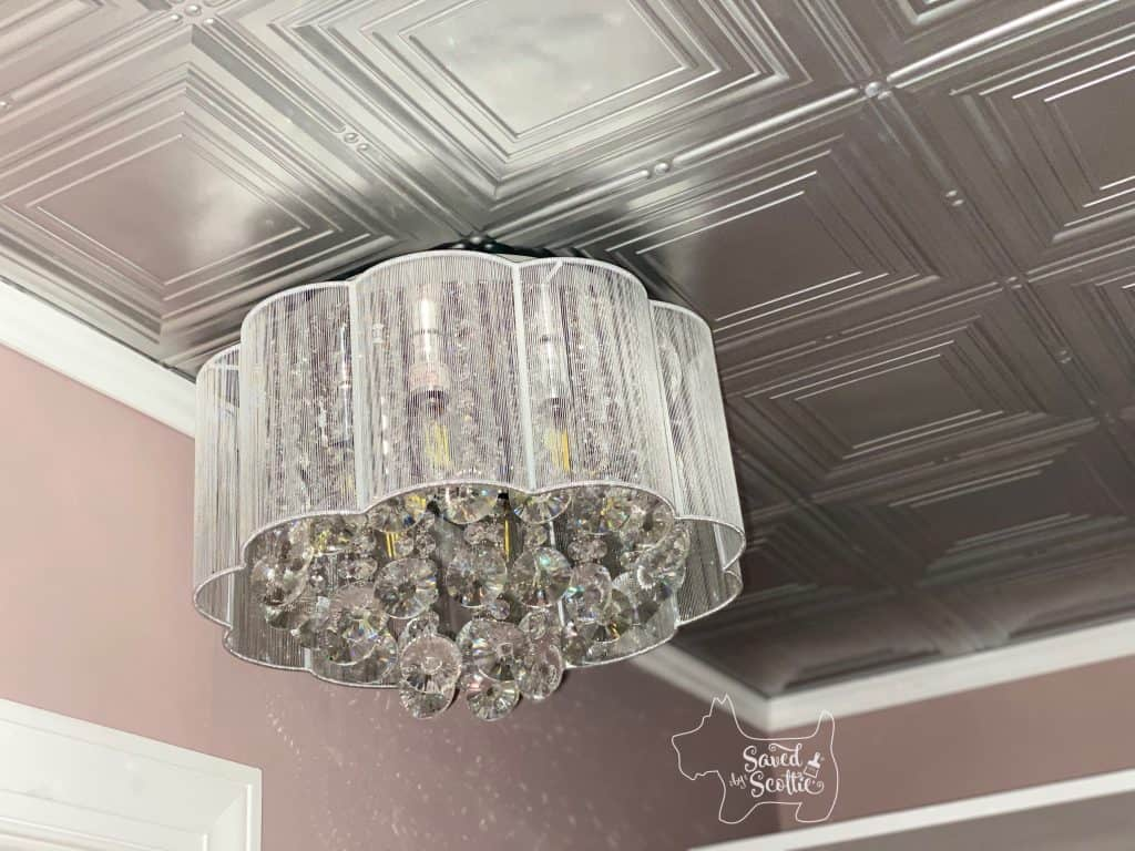 close up of unlit crystal chandelier mounted on ceiling of Fasäde silver painted panel