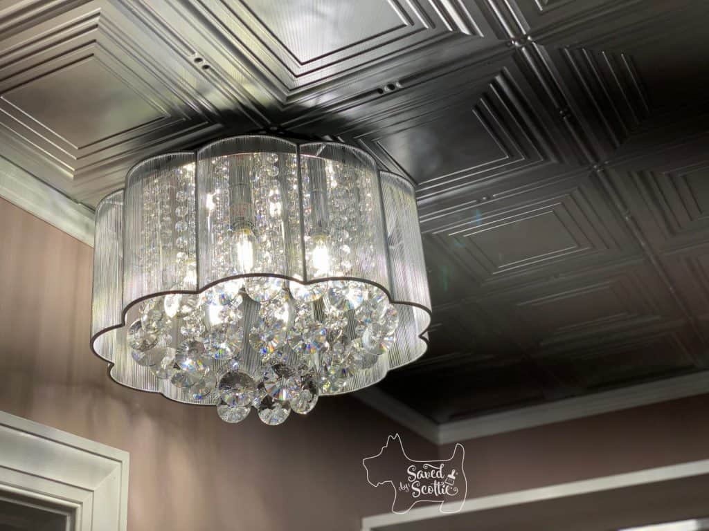 close up of lit crystal chandelier mounted on ceiling of Fasäde silver painted panel