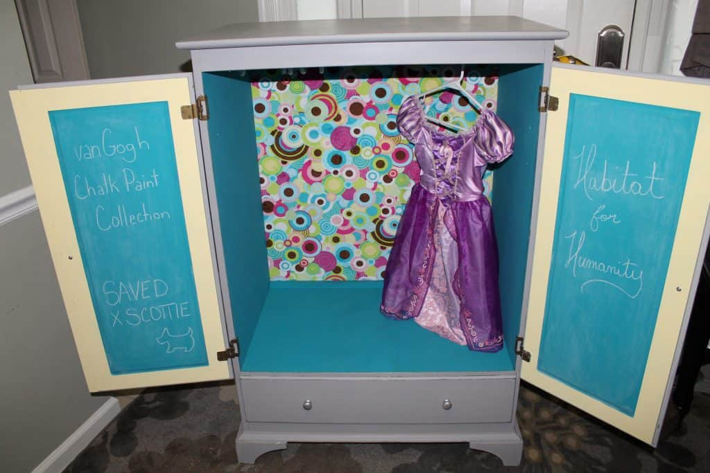 grey cabinet open with colorful circles in back, child's costume hanging and interior painted teal and yellow.