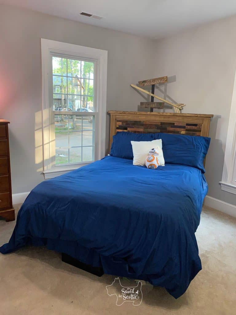long view of diy headboard and bed with new comforter cover and bed skirt.