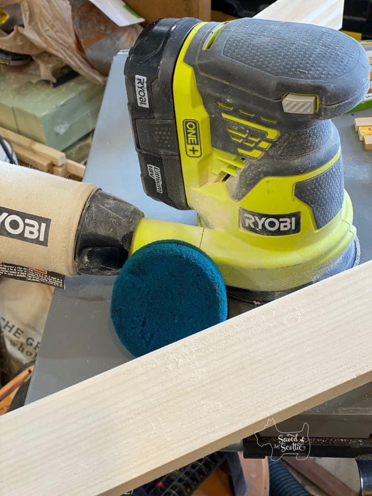 ryobi orbital sander stain applicator sponge and sanded piece of common board.