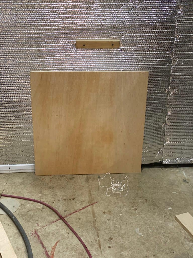 piece of plywood leaning against a wall in a workshop setting