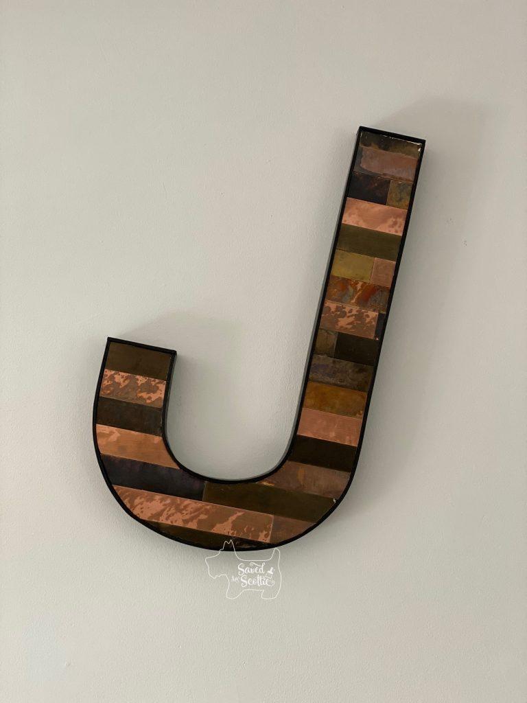Letter J hanging on a wall tilted backwards