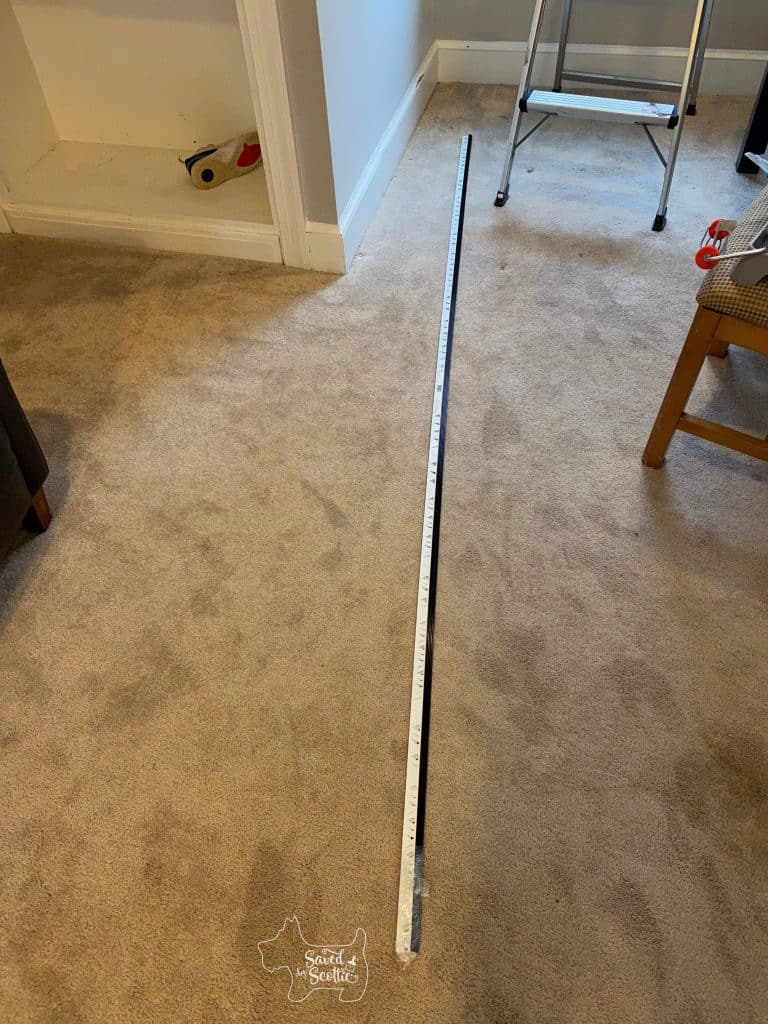 long pieces of metal tile trim laying on a carpeted floor of a bedroom