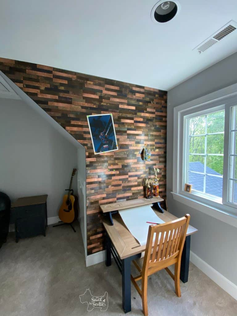 long view. of metal tile wall with desk. in place poster and facemask on wall held up with magnets