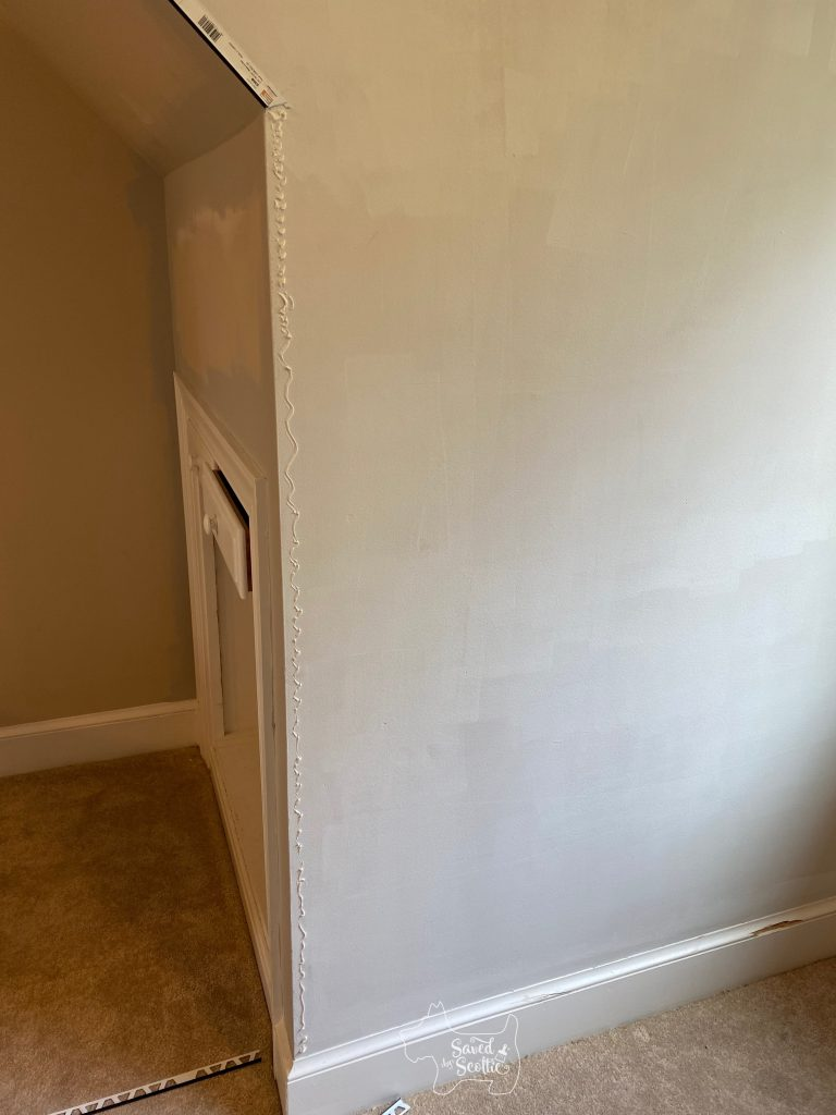 accent wall with construction adhesive along the edge ready for trim to be placed on it.