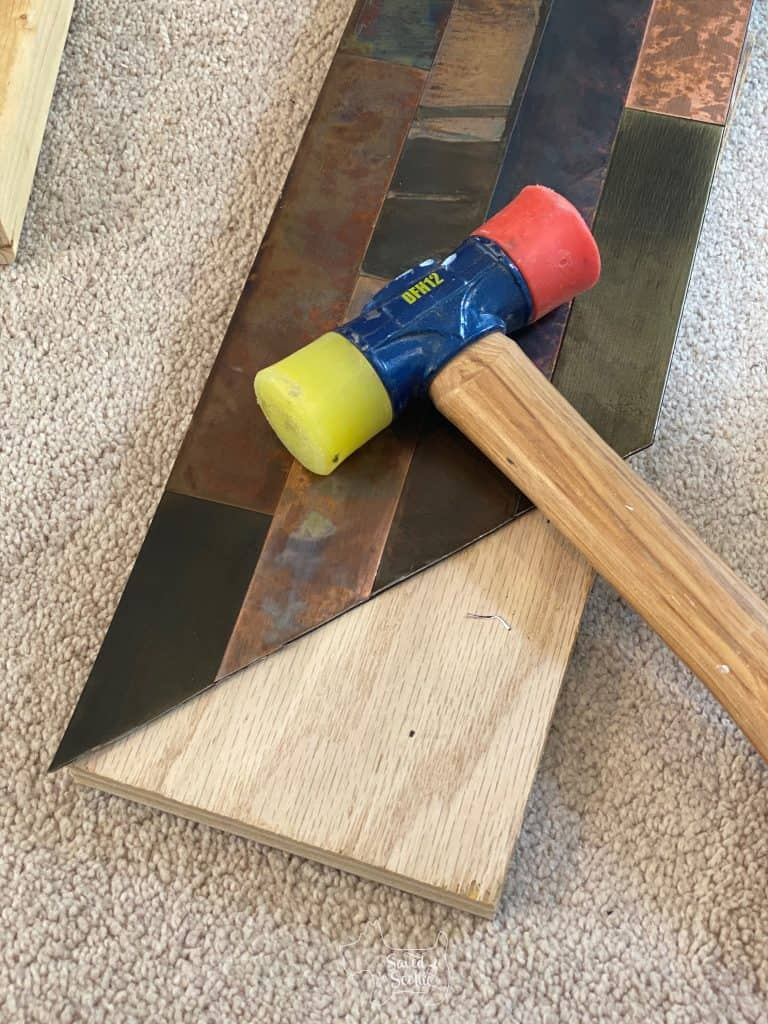 close. up of metal tile and a double headed rubber mallet